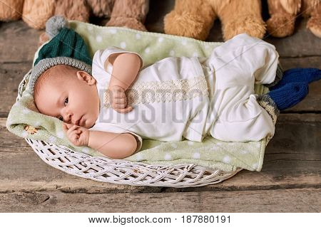 Infant in basket, wooden background. Child wearing knitted socks. Baby health tips.