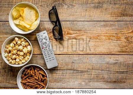 film whatching party with glasses, crumbs, chips and pop corn on wooden background top view mockup