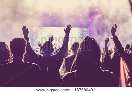 Crowd Of Audience With Hands Raised At A Music Festival