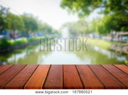 Selected focus empty brown wooden table and river nature or forest blur background with bokeh image. for your photomontage or product display.