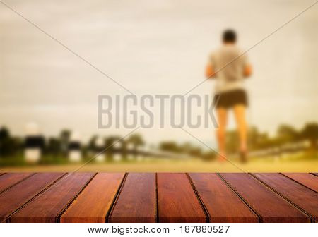 Selected focus empty wooden table and view of sport man blur background with bokeh image. for your photomontage or product display.