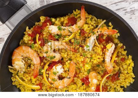 Delicious paella in panwith shrimps from above.
