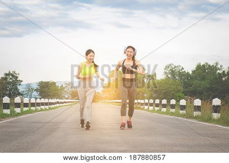 Runners - two women running outdoors training. Exercising female athletes jogging outside on nature smiling happy. Multiracial Asian and Caucasian woman in healthy lifestyle.