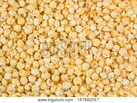 Scattered caramel popcorn, texture background. Backdrop for a web site, scrapbooking, packaging