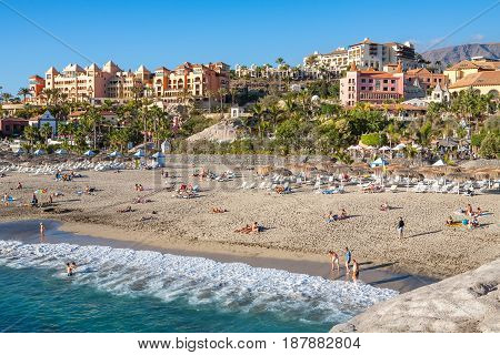 COSTA ADEJE TENERIFE SPAIN - JANUARY 31 2012: Many people sunbathing on Playa del Duque beach. Canary Islands