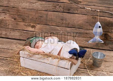 Baby fisherman is sleeping. Kid, hay and wood background. How to start fishing.