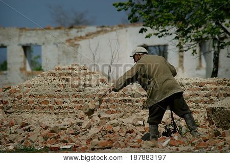 Petriki - May 04: The man dismantles the farm on the bricks. The structure remained after the USSR. Bricks go as a salary on the collective farm, on May 04, 2004 in the village of Petriki Cherkasy region, Ukraine.