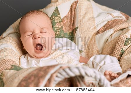 Caucasian baby yawning. Small child with mouth open. Tired signs in infant.