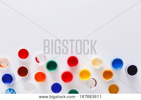 Color gouache jars on white background, top view, copy space