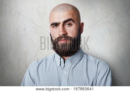 A Confident Bald Male With Thick Black Eyebrows And Beard Wearing Checked Shirt Having Gloomy Expres