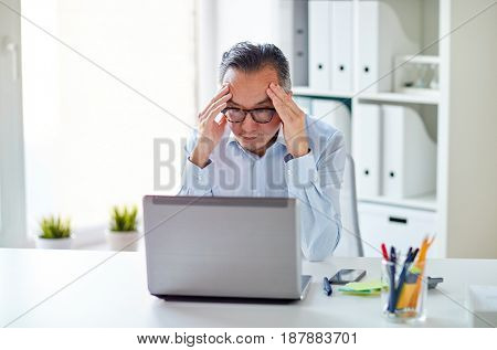 business, deadline, stress, people and technology concept - businessman in eyeglasses with laptop computer at office