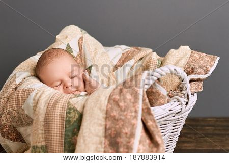 Infant boy with closed eyes. Cute kid touching his face. Baby skin care tips.