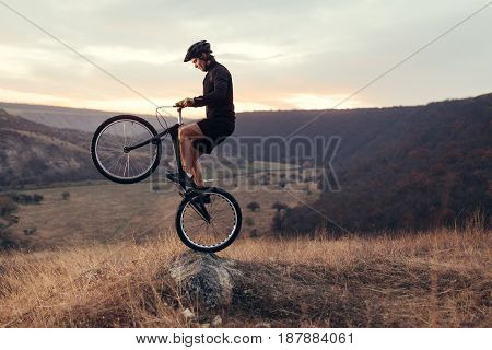 Side view of young man in sportive outfit doing tricks with bicycle while riding against landscape.