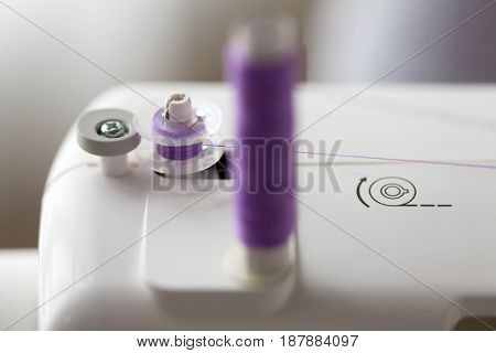 craft and tailoring concept - thread spools on sewing machine