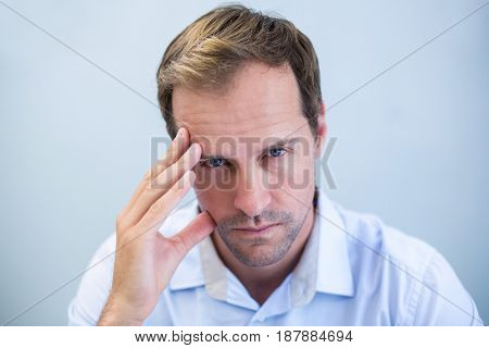 Portrait of tensed doctor with hand on forehead in clinic