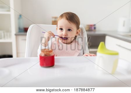 food, child, feeding and people concept - little baby girl with spoon sitting in highchair and eating puree from jar at home kitchen