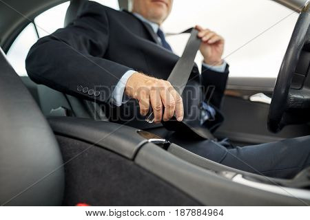 transport, business trip, safety and people concept - senior businessman fastening seat belt before driving car