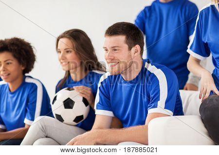 friendship, leisure, sport and entertainment concept - happy friends or football fans with ball watching soccer at home