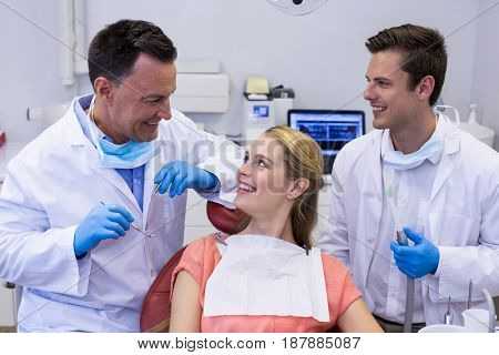 Dentists interacting with female patient in clinic