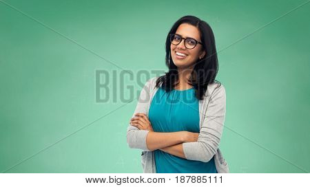 education, school and people concept - happy smiling young indian student woman or teacher in glasses over green chalkboard background