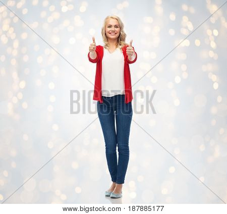 gesture, fashion and people concept - happy smiling young woman in red cardigan showing thumbs up over holidays lights background