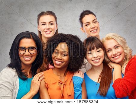 diversity, ethnicity and people concept - international group of happy smiling different women hugging over gray concrete wall background