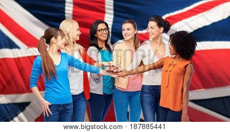 diversity, ethnicity and people concept - international group of happy smiling different women holding hands together over british flag background