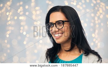 vision, portrait and people concept - happy smiling young indian woman in glasses over holidays lights background
