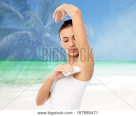 hygiene, bodycare and people concept - beautiful young woman applying antiperspirant or stick deodorant over exotic beach background with double exposure effect