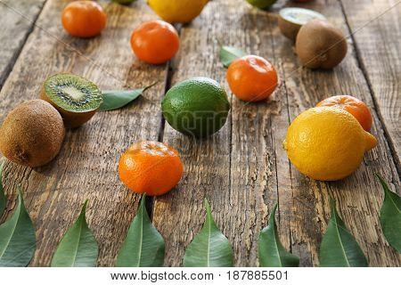 Appetizing fresh citrus fruits with kiwi on wooden background