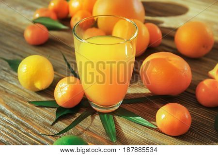 Glass of juice and fresh citrus fruits on wooden background