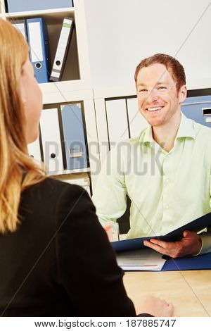 Man and woman talking during a job interview with curriculum on the man´s hand