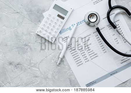health care billing statement with doctor's stethoscope on stone table background top view mock-up poster