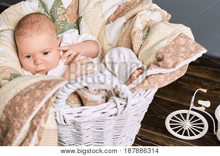 Baby boy whistling. Basket, blanket and infant. Music in the genes.