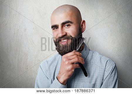 Attractive Yound Balded Barber With Thick Black Beard And Mustache Smiling While Holding Straight Ra