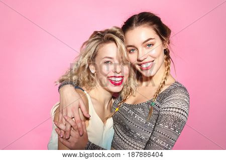 Smiling embracing female friends looking at camera on the pink background.