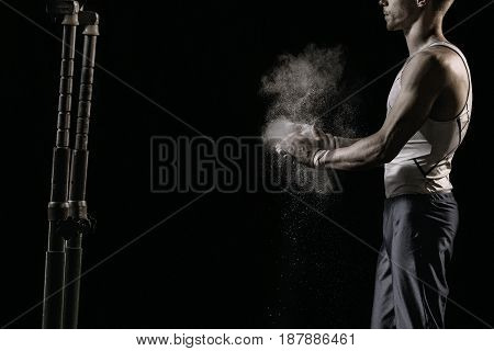 Male athlete rubs hands with talcum powder in front of gymnastic parallel bars
