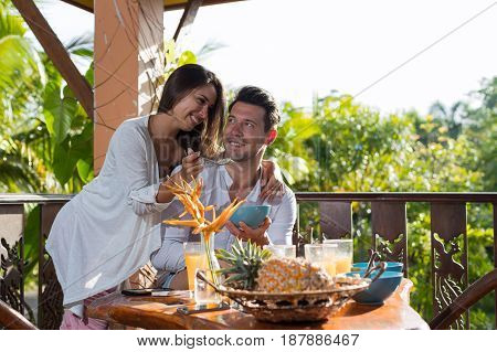 Couple On Summer Terrace Having Breakfast, Woman Feeding Man With Porridge In Morning Eating Outdoors With View On Tropical Forest