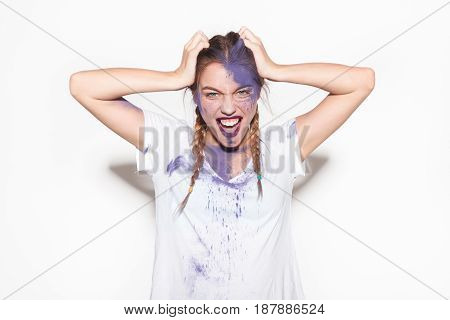 Woman in white t-shirt posing with dry paint on face and looking at camera on white background.