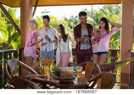 People On Summer Terrace Having Breakfast Use Cell Smart Phones, Woman And Man Eat Talking In Morning Outdoors Natural Light With View On Tropical Forest