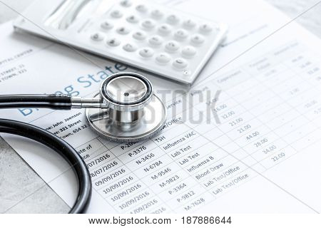 health care billing statement with doctor's stethoscope on stone table background