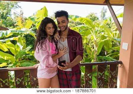 Couple Use Cell Smart Phone On Summer Terrace, Man And Woman Embracing Chatting Online Outdoors Happy Smiling Over View On Tropical Forest