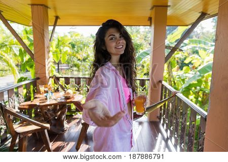 Woman On Summer Terrace Hold Hand Drink Orange Juice, Happy Smiling Girl In Morning Welcoming Gesture Outdoors Over Tropical Forest View