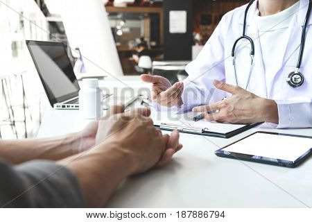 Healthcare and Medical concept patient listening intently to a female doctor explaining patient symptoms or asking a question as they discuss paperwork together in a consultation.