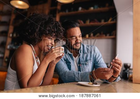 Young Couple At Coffee Shop Looking At Smart Phone