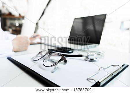 View of stethoscope and equipment on foreground table with doctor using computer keyboard in clinic.