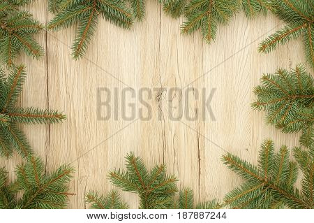 Christmas frame out of fir tree twigs on brown wooden background with lots of copy space.