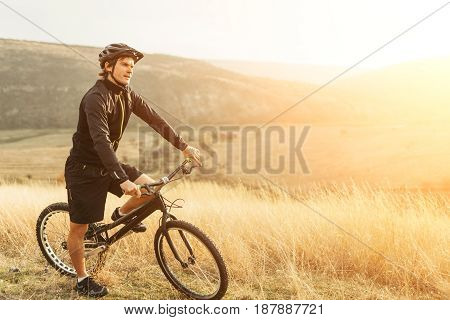 Person in the field looking away sitting on a bike. Horizontal outdoors shot.