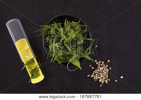Medical marijuana in pill organizer and seeds on black background top view. Alternative medicine.