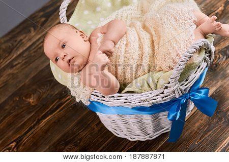 Caucasian infant in a basket. Baby boy wrapped in blanket.